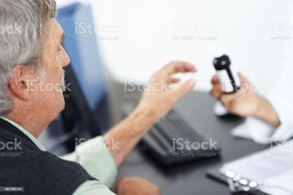Retired man given a medicine bottle by doctor royalty-free stock photo