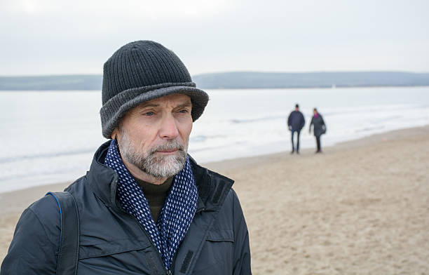 Retired man on beach in the winter stock photo