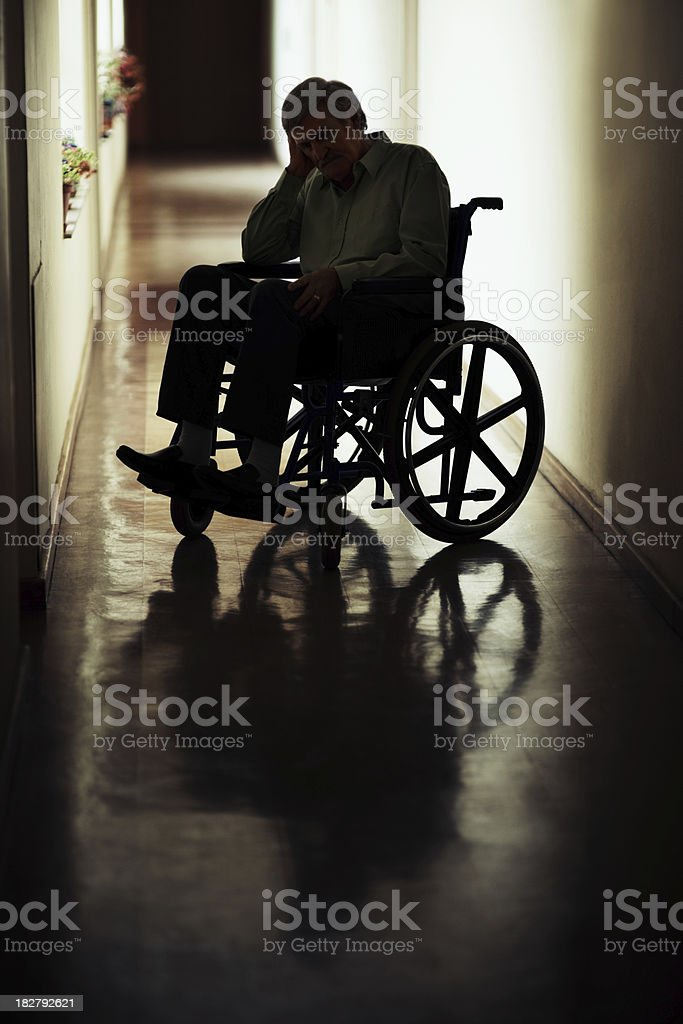 Retired man on wheelchair in a hospital corridor royalty-free stock photo