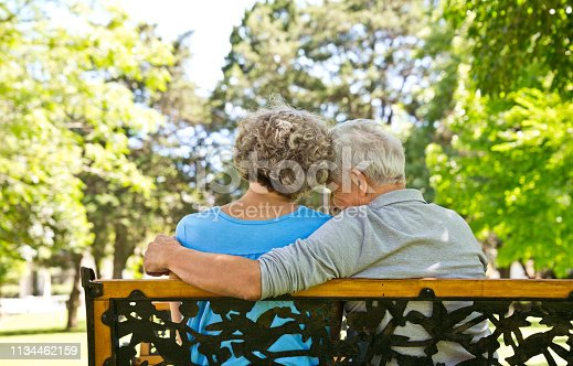 Retired man sitting with arm around woman at nursing home. Rear view of senior couple is relaxing on bench at back yard. They are spending leisure time.