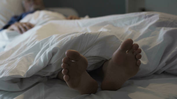 retired man sleeping in bed, nasty smell and discomfort due to foot fungus - old man feet stock photos and pictures