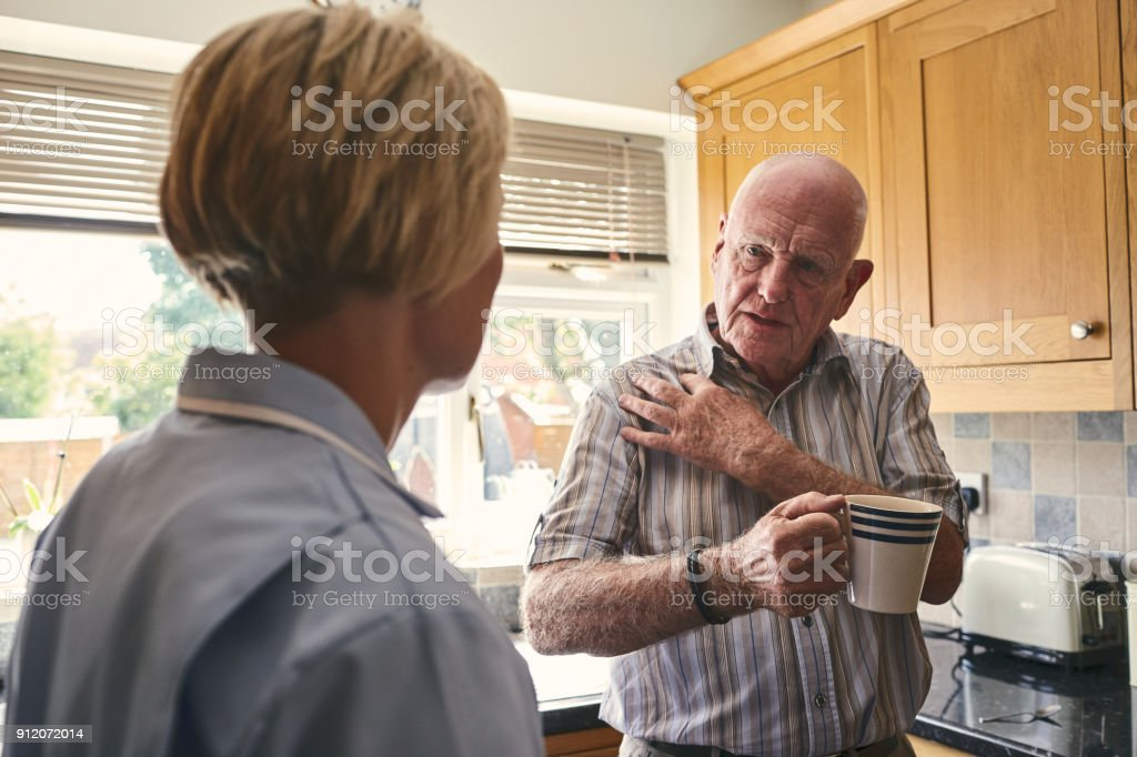 Retired man with aching shoulder talking to home carer stock photo