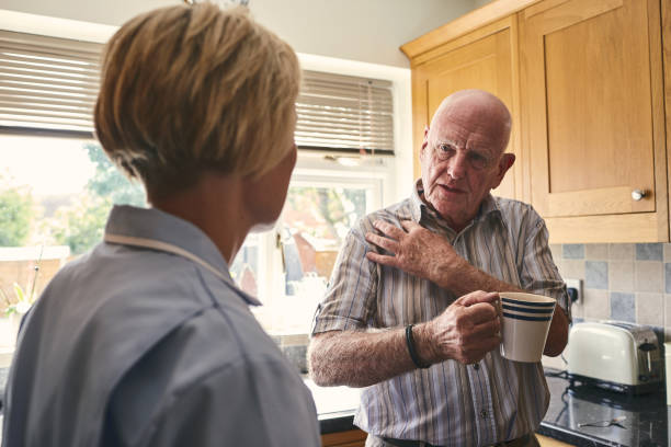 retired man with aching shoulder talking to home carer - spalla giuntura foto e immagini stock