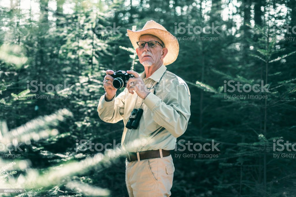 Retired man with camera and binocular in forest. foto stock royalty-free