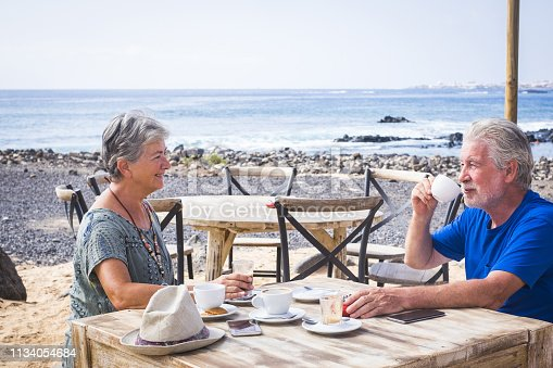 Retired mature couple enjoying a beautiful sunny day at the beach drinking coffee and cappuccino together. Happy senior woman and man sitting at the bar with wooden tables by the sea. Blue sky and horizon in background