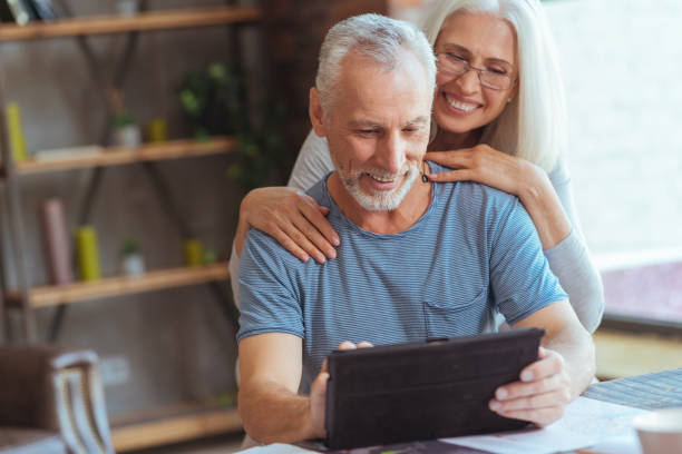 Retired positive man using tablet with his wife stock photo