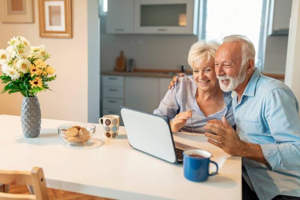 Couples aînés retraités achetant des cadeaux pour leurs petits-enfants en ligne - Photo