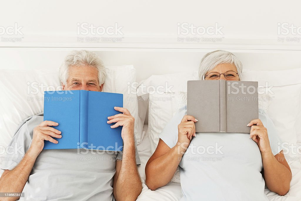 Retired senior couple in bed with books royalty-free stock photo