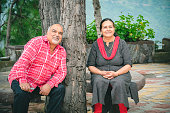 An Asian/Indian, beautiful, happy retired senior couple sits under a tree at a resort in the mountains of Himachal Pradesh.