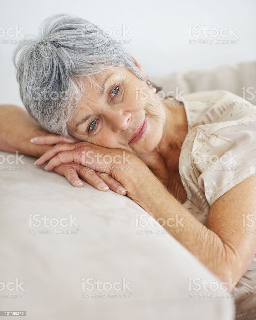 Retired senior lady relaxing on couch royalty-free stock photo