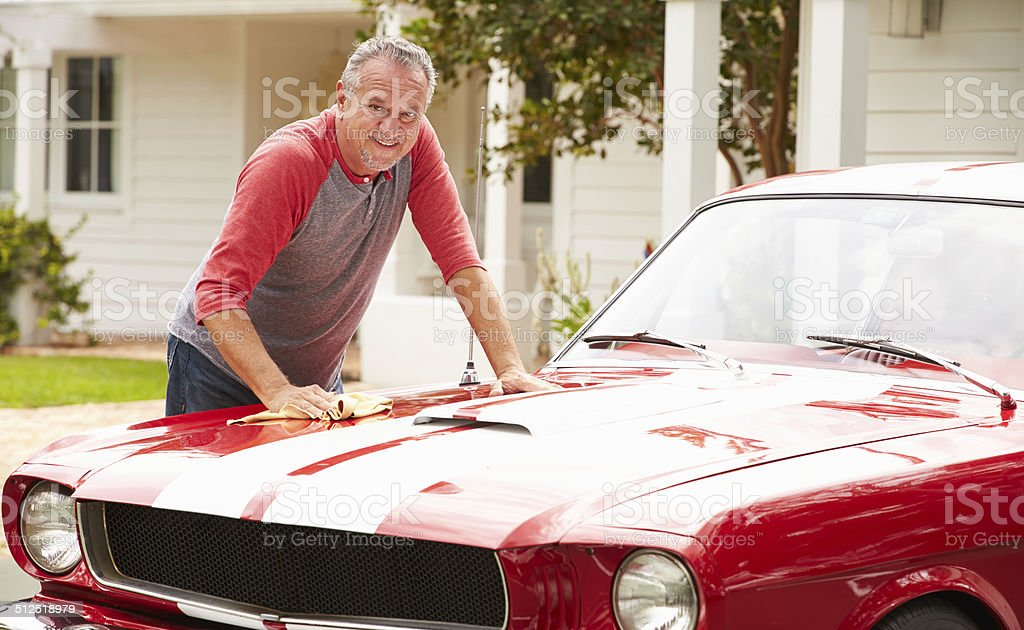 Retired Senior Man Cleaning Restored Classic Car stock photo