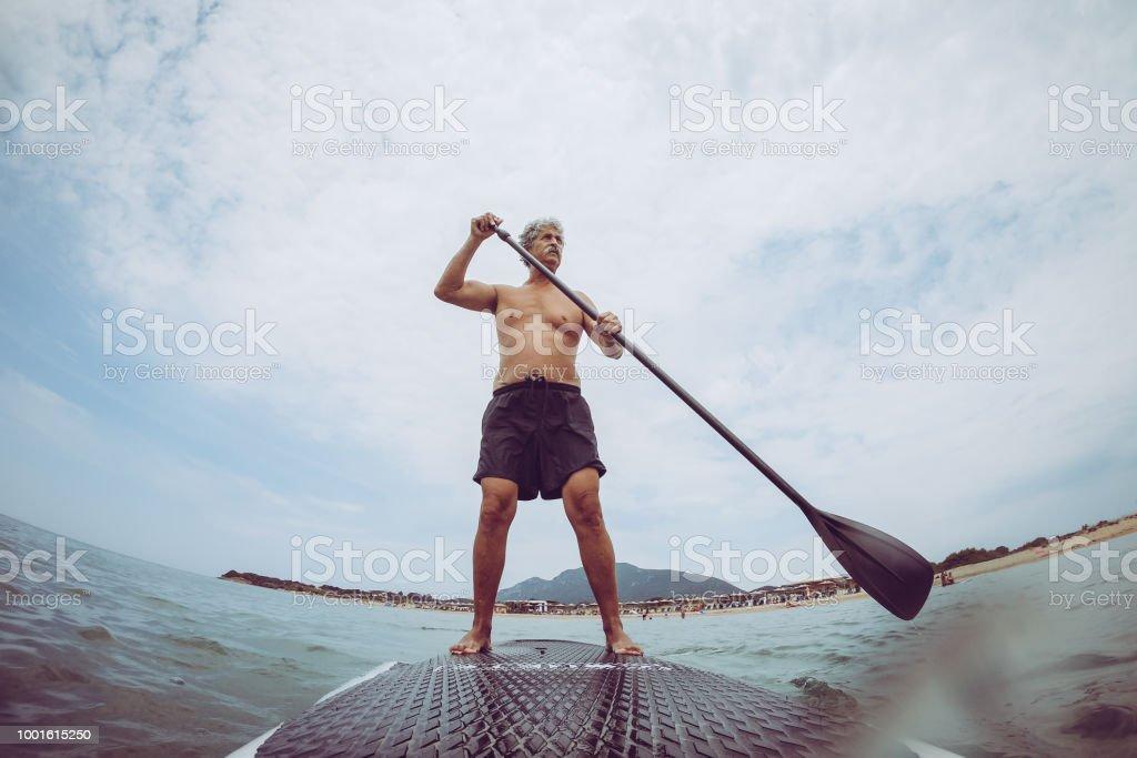 Retired senior man enjoying the day on the sea Senior man sails on a SUP board on the sea. Active Lifestyle Stock Photo