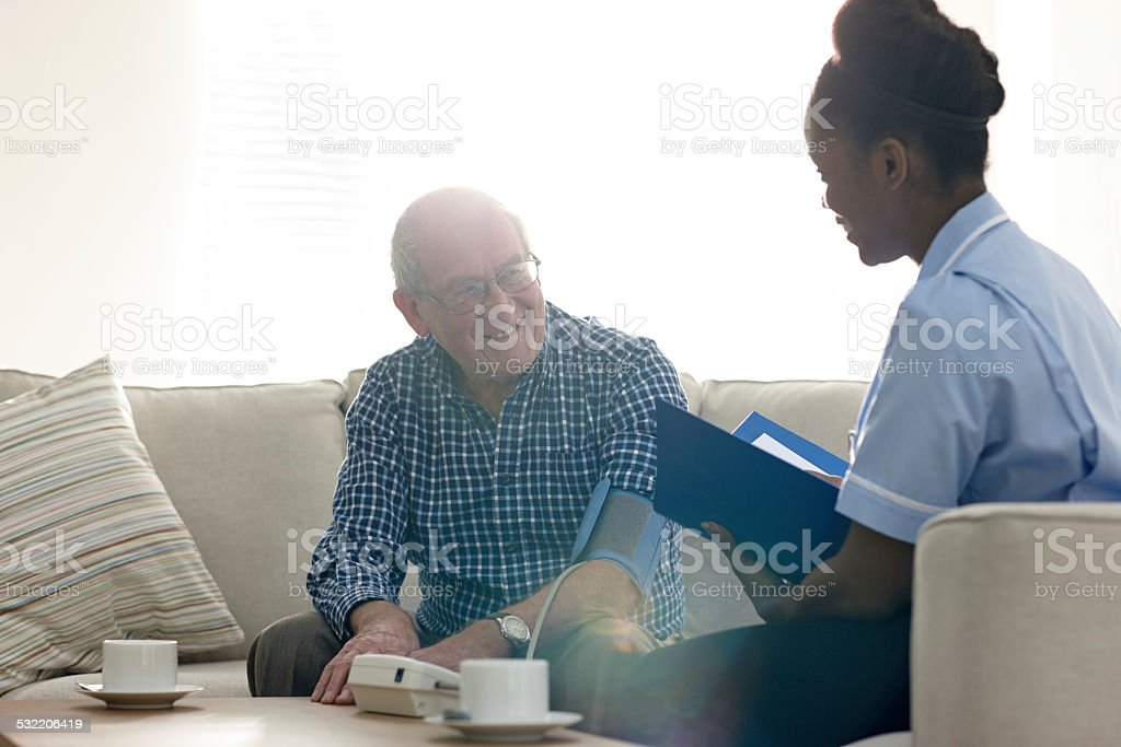 Retired senior man having health check with nurse at home stock photo