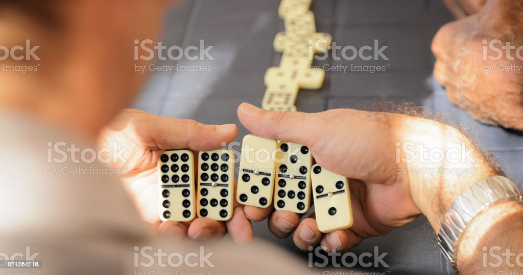 Retired Senior Man Playing Domino Game With Friends stock photo