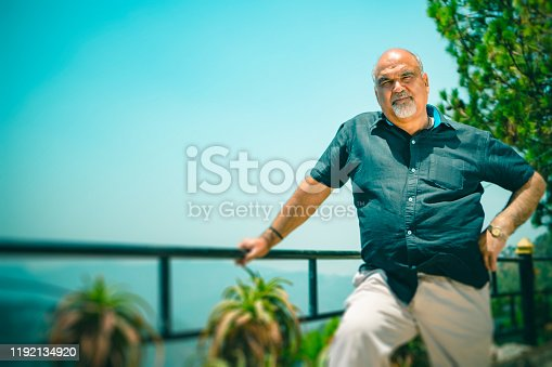 An Asian/Indian happy retired senior man poses for a photo and looks at the camera at a resort in the mountains of Himachal Pradesh.