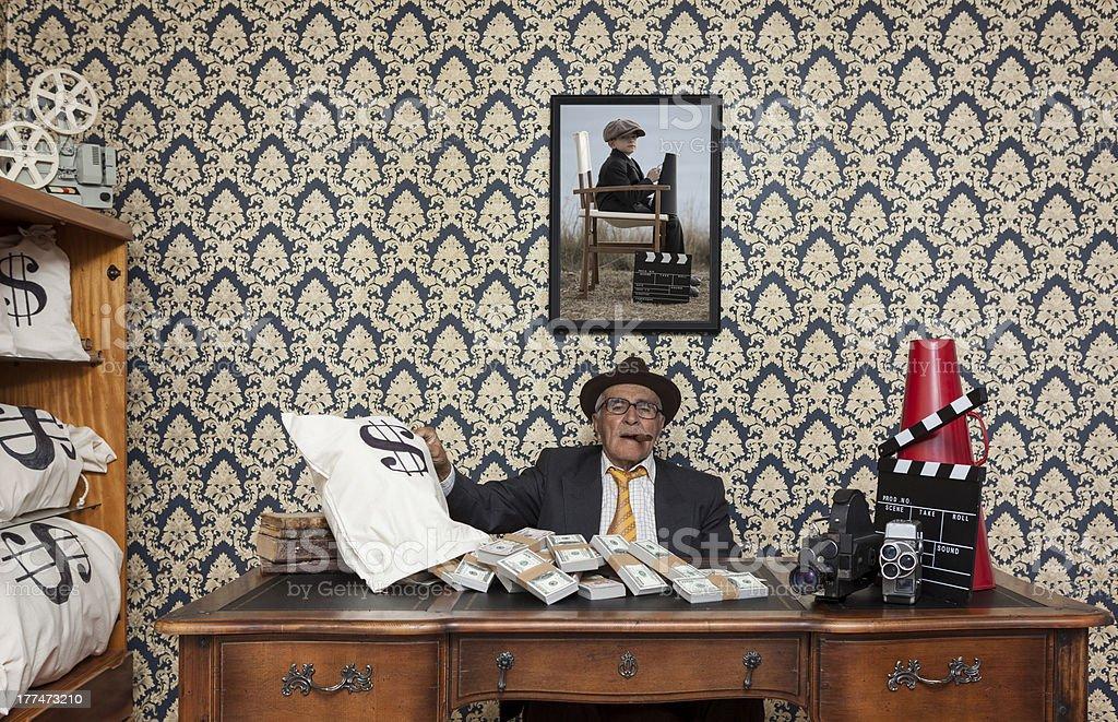 Retired senior man posing with dollar bills and cinema equipments stock photo
