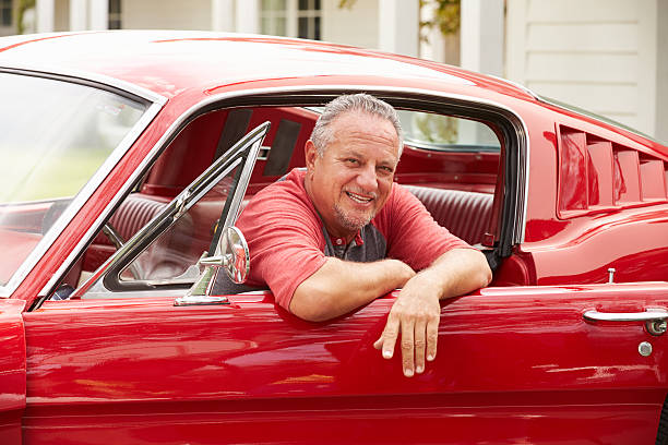 ehemaliger alter mann sitzt in einem restaurierten classic car - alten muscle cars stock-fotos und bilder