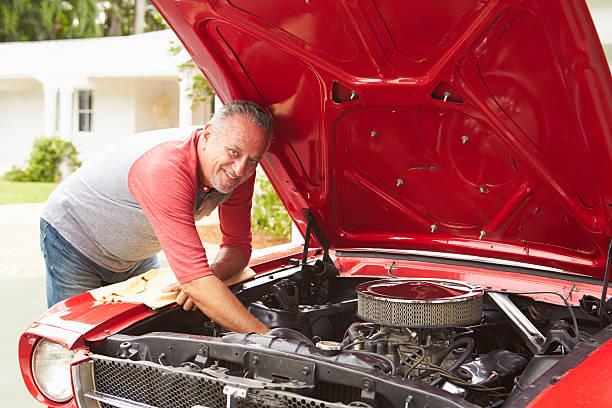 ehemaliger senior mann arbeitet auf renovierten classic car - 1m coupe stock-fotos und bilder