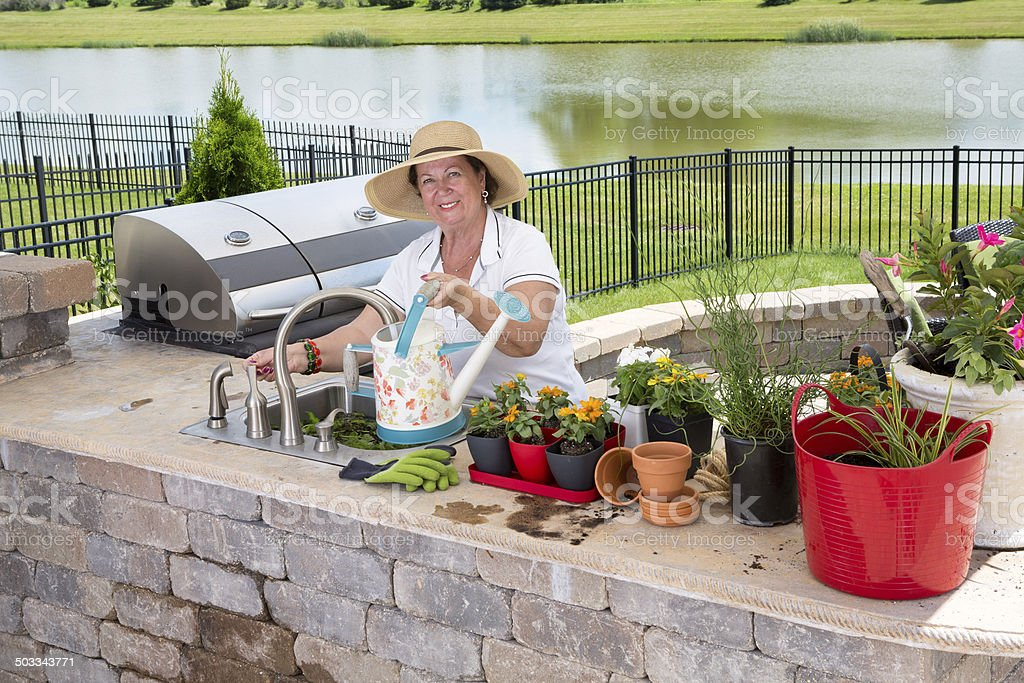 Retired senior woman gardening, in a brick patio stock photo