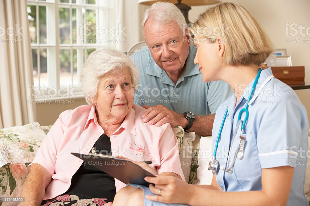 Retired Senior Woman Having Health Check With Nurse At Home stock photo