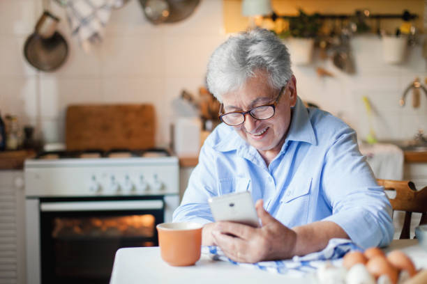 Retired woman is using mobile phone, smiling at cozy home kitchen. Grandmother has coffee break in cooking. stock photo