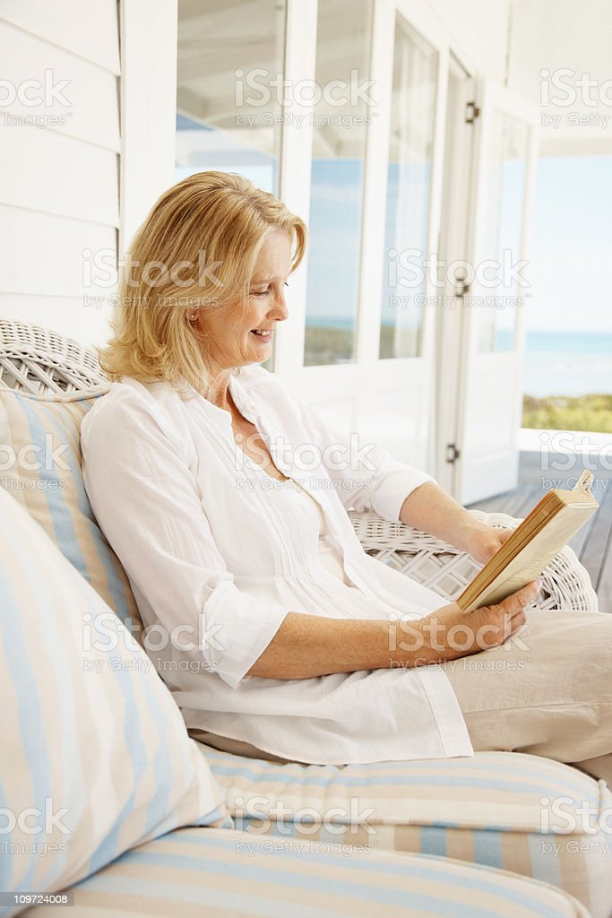 Retired woman on a vacation reading book royalty-free stock photo