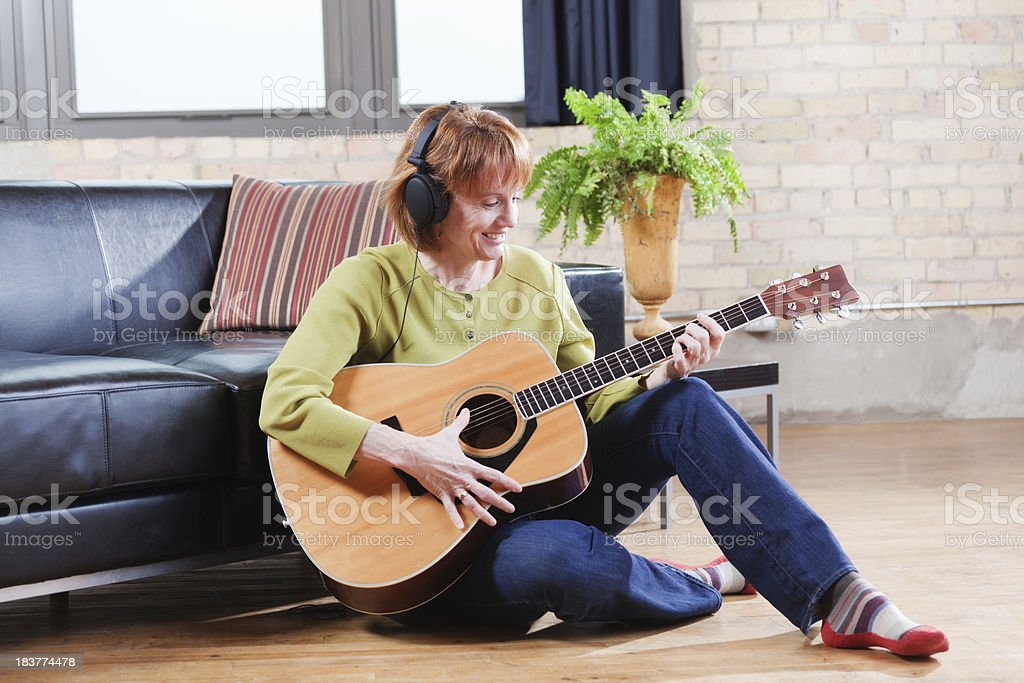 Retired Woman Playing Guitar in Loft Condominium Home Hz royalty-free stock photo