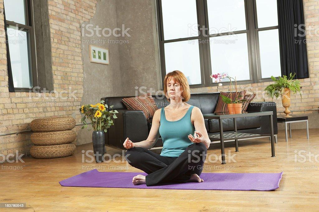 Retired Woman Practicing Yoga in Loft Condominium Home royalty-free stock photo