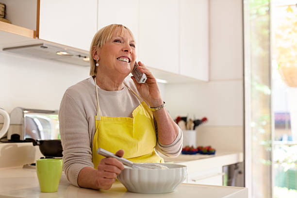 "Retired woman preparing food at home ""Happy senior woman at home, cooking in kitchen and talking on the phone"" cordless phone stock pictures, royalty-free photos & images"