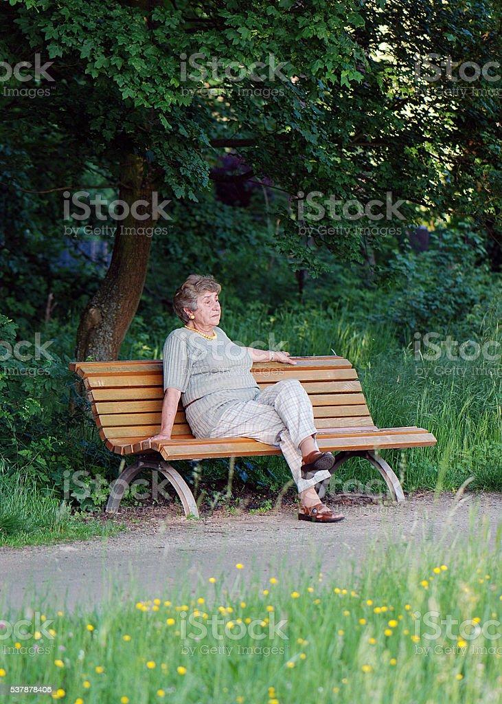 Retiree on park bench stock photo