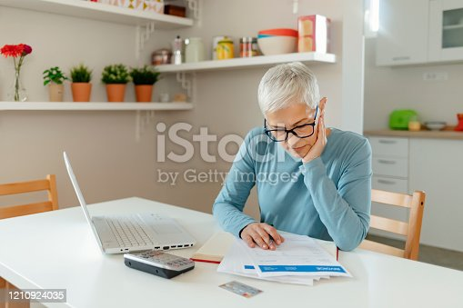 Stressed Senior Woman Worried About Bills and Debt Doing Banking and Administrative Work at Home. Gray Hair Woman Doing Homefinances. Mature Woman Working With Documents in the Kitchen