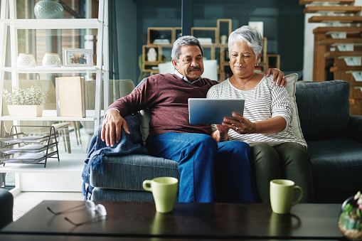 Shot of a mature couple using a digital tablet while relaxing at home