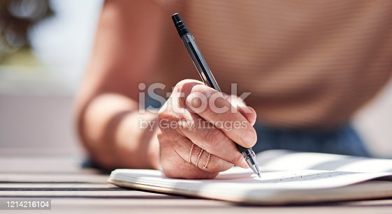Cropped shot of an unrecognizable senior woman writing in her book outside on the balcony at home