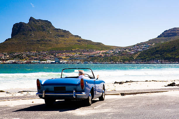 Retirement hobby Elderly man sits in his vintage British sports car, watching the sea and a fishing harbor across the bay. hout stock pictures, royalty-free photos & images