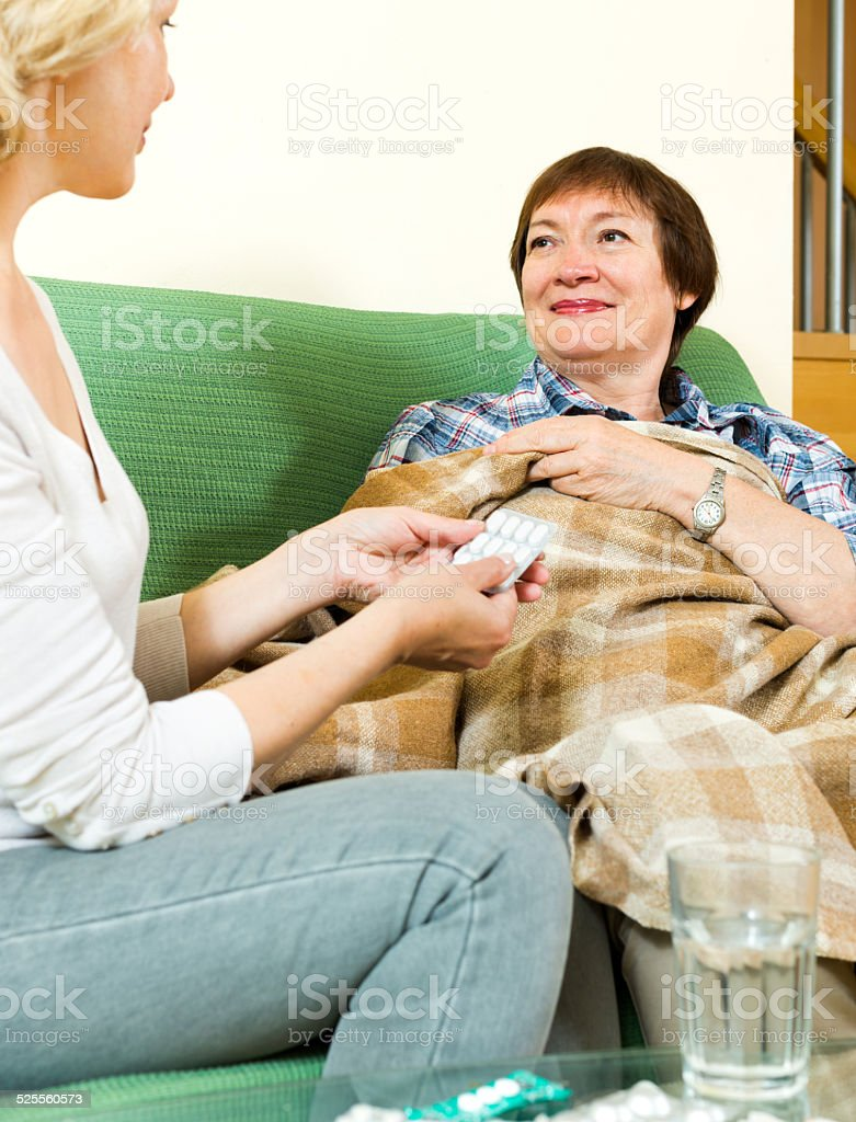 Retirement home  employee gives pills woman stock photo