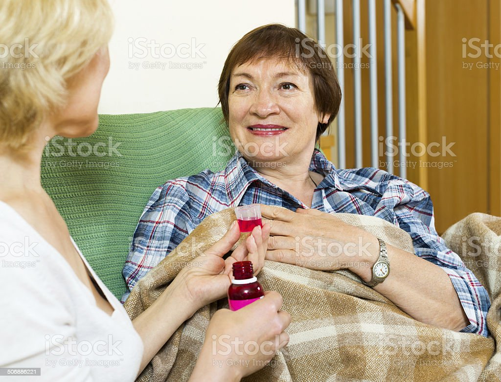 retirement home employee offering  mixture to aged patient stock photo