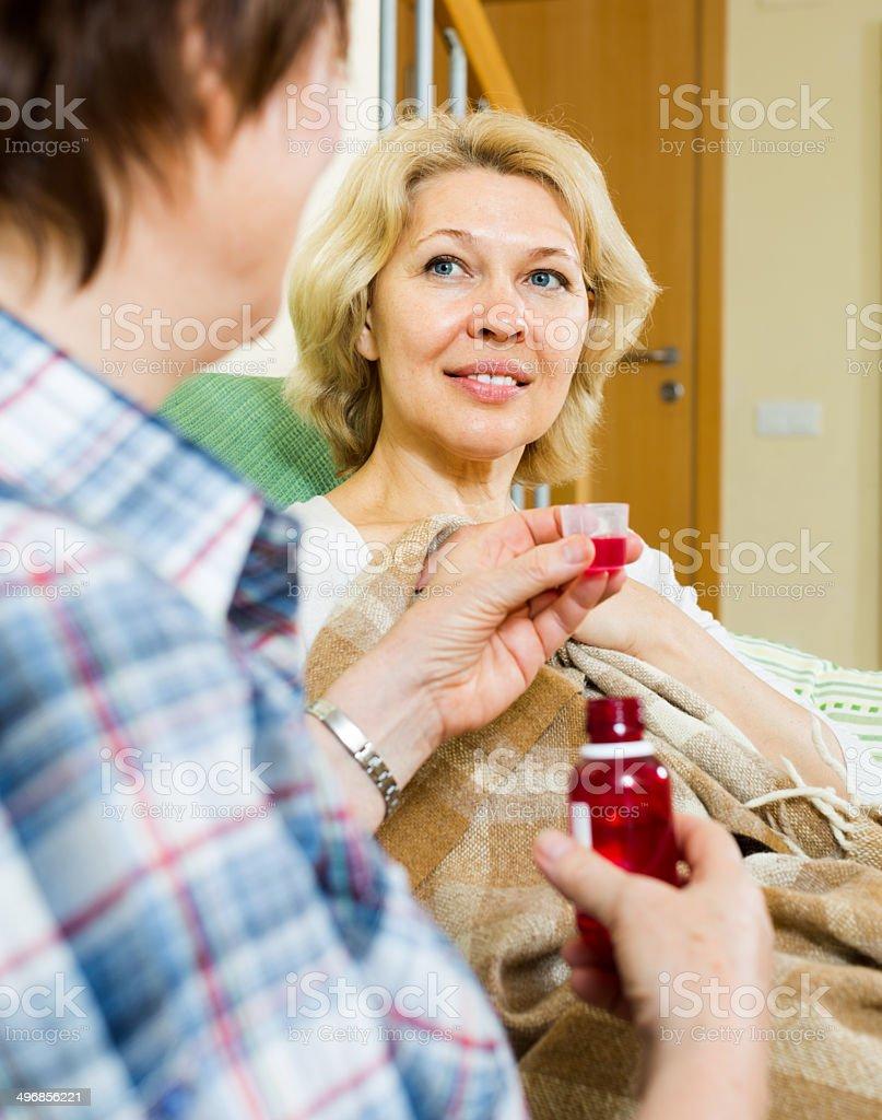 retirement home employee offering  mixture to  patient stock photo