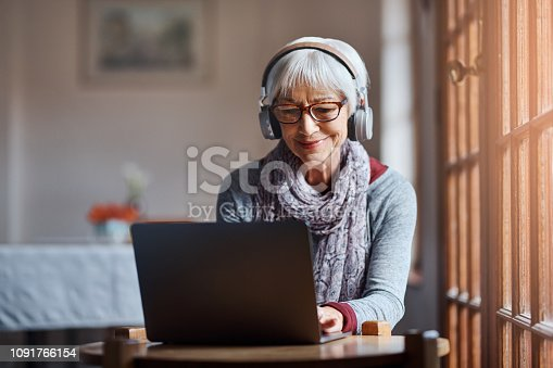 Shot of a senior woman using a laptop and headphones in a retirement home