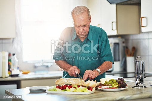 Cropped shot of a senior man making lunch in his kitchen at home