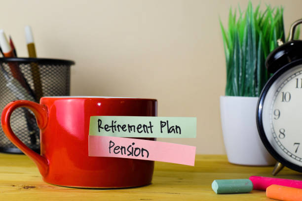 Retirement Plan and Pension. Handwriting on sticky notes in clothes pegs on wooden office desk stock photo