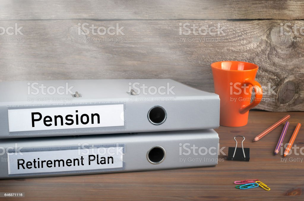Retirement Plan and Pension - two folders on wooden office desk stock photo