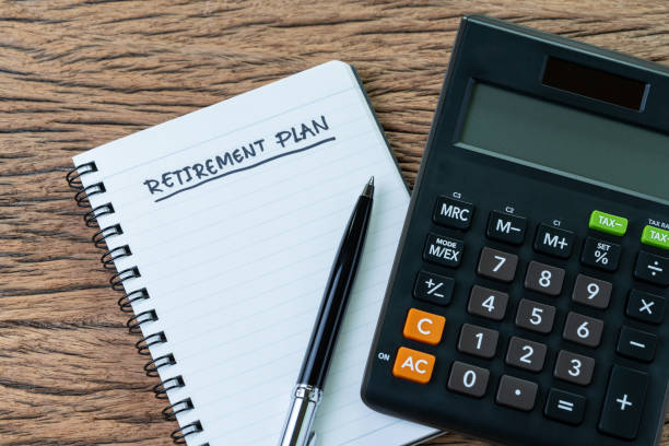 retirement planning concept, calculator with empty notepad with pen and handwriting underline headline as retirement plan on wood table, plan of saving and investment for expense after retire life - ira stock pictures, royalty-free photos & images