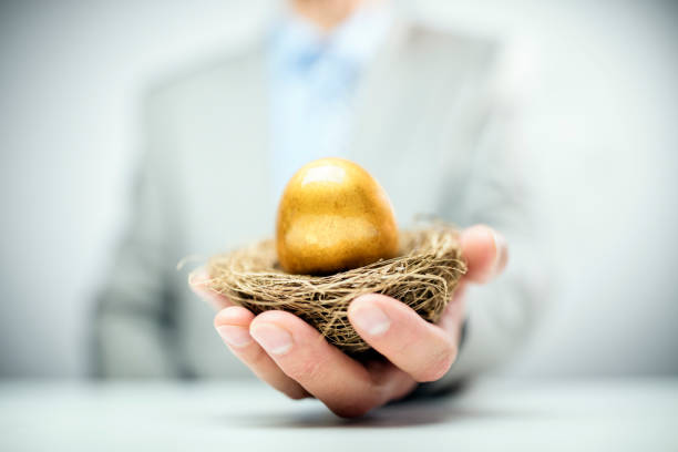Retirement savings golden nest egg in businessman hand stock photo