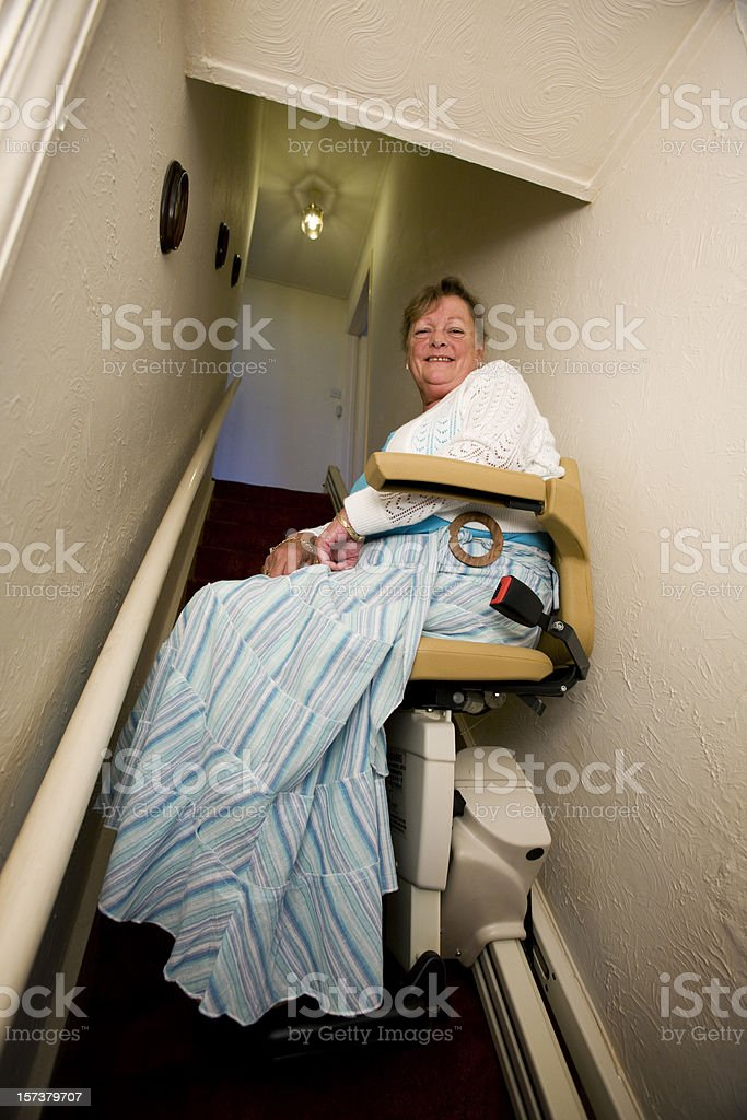 retirement: senior woman living at home using her stair lift royalty-free stock photo