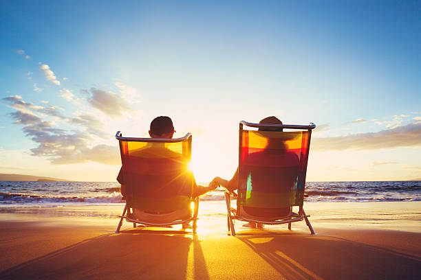 retirement vacation concept, mature coupe watching the sunset - retirement stock photos and pictures