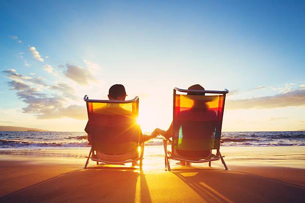 Concepto de jubilación vacaciones, maduras Coupe viendo la puesta de sol - foto de stock