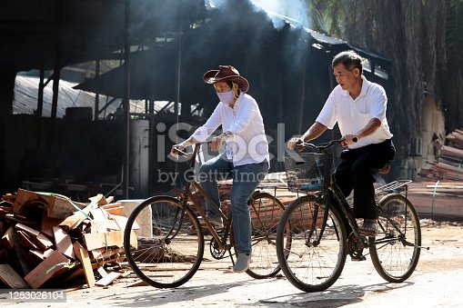 A senior couple are riding antique bicycle for commuting from one place to another in between task at their organic mushroom farm in Malaysia. Plank collection are meant for burning to produce energy and steam for mushroom packs sterilization.