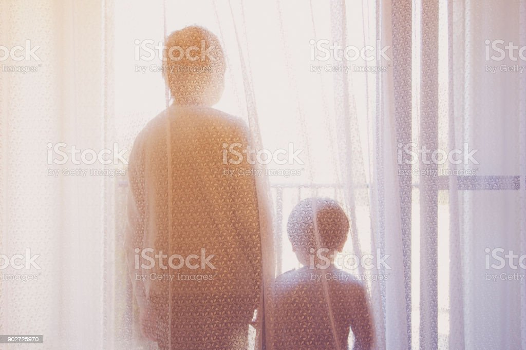 Retreating figures of grandmother and her grandson looking outside over balcony at home stock photo