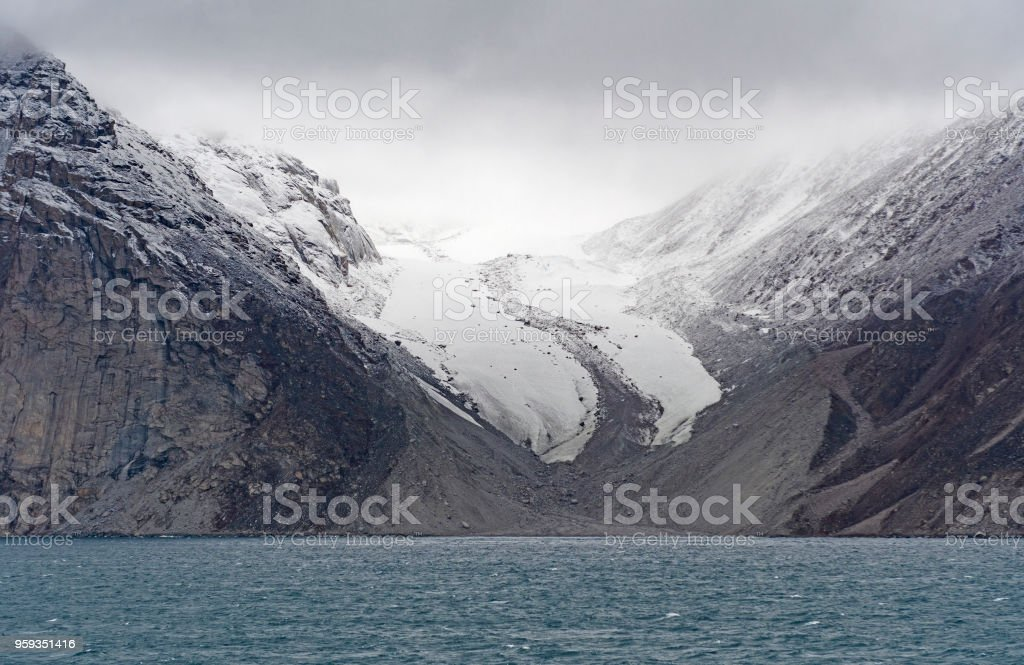 Retreating Glacier Coming out of the Clouds stock photo