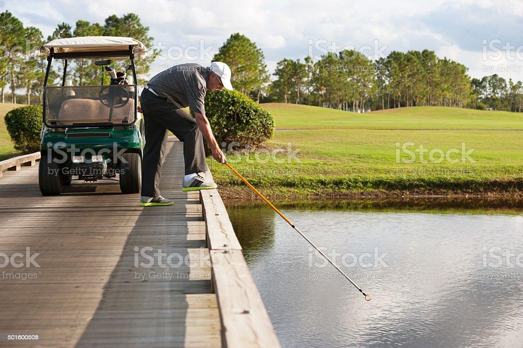 retreiving golf ball from water hazard stock photo